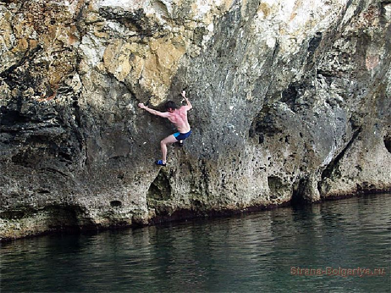 Один из любителей экстремальных видов спорта на скале над водой